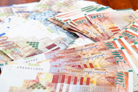 sheqel: Two hundred and one hundred shekel bank notes against wood background. Concept photo of money, banking ,currency and foreign exchange rates.