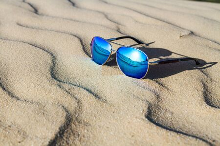 Sunglasses on the sand , summer desert is reflected in the glasses.