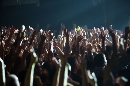 illuminated: Crowd at concert and blurred stage lights . Close up of photographing with smartphone during a concert .
