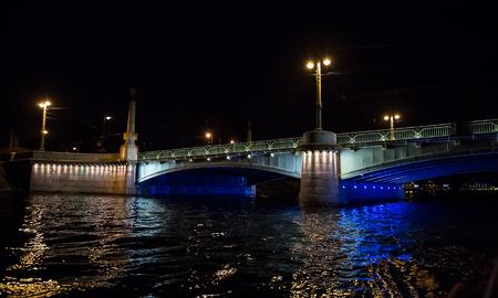 Night cityscape with river and bridge in Saint-Petersburg . Lantern lights on the bridge . Stock Photo