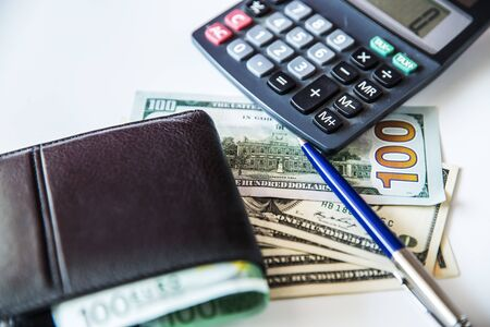 Currency in the wallet and on the table. Calculator and pen.