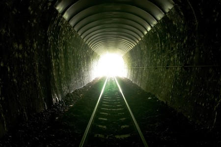 old train: Light at the entrance of train tunnel. Stock Photo