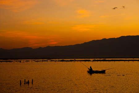 Fisherman in Payao lake, north of Thailand photo