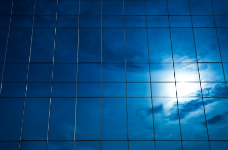 Reflection of cloud and sun in  glass building photo