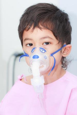 asma: Ni�o con un instrumento m�dico en su cara Foto de archivo