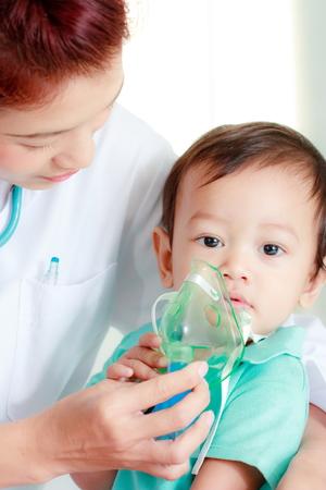 Doctor putting medical mask on babys face
