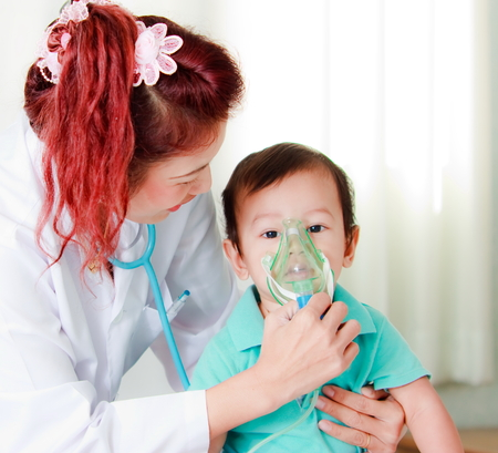 sick baby: Doctor putting medical mask on babys face