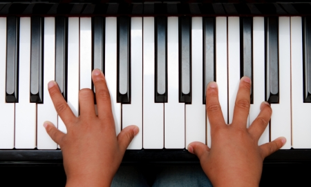 fortepian: Ręce dzieciak na klawiaturze fortepianu Zdjęcie Seryjne