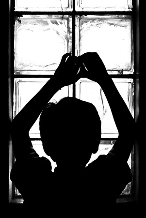 Boy in shadow looking to light photo