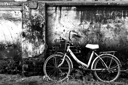 brick background: Old bicycle in black and white Stock Photo
