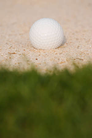 Golf ball on sand bunker photo