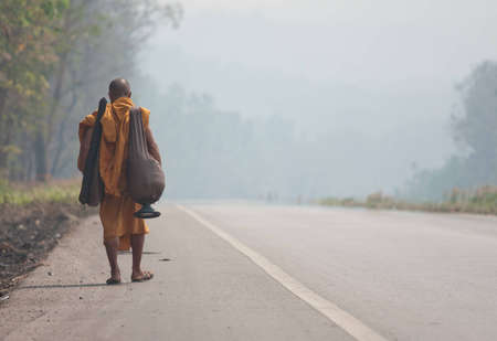Buddhist monk take to the road in forest as a form of meritamaking photo