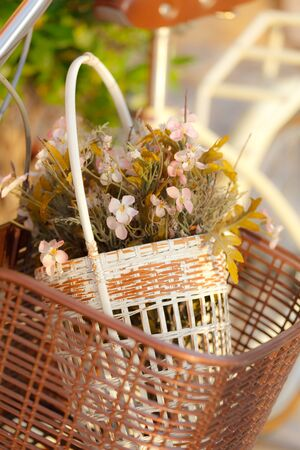 Colorful fake flower in bicycle basket photo