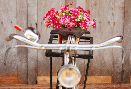 Colorful fake flowers on old style bicycle and rain drops
