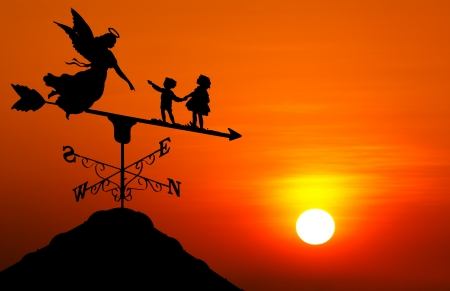 Angle and kids on weather vane at sunset photo