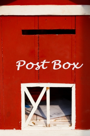Red wood postbox and postcard inside photo