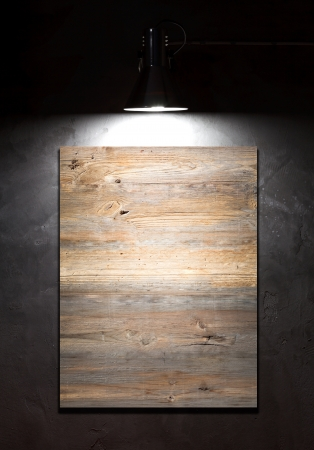 Light on blank board over concrete wall