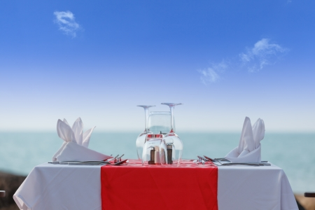 dining table: Luxury dinner table on beach in blue sky