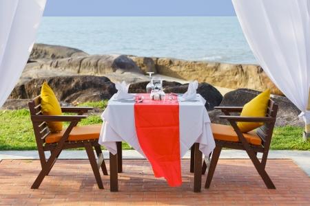 Table for dinner beside beach at sunset Standard-Bild