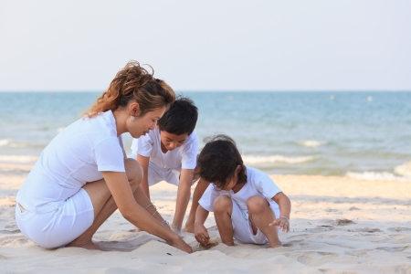 熱帯のビーチでアジアの家族再生