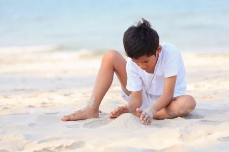 Asian boy play on beach in golden sunlight