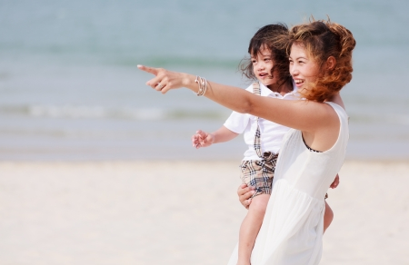 Asian mother and son playing on tropical beach photo