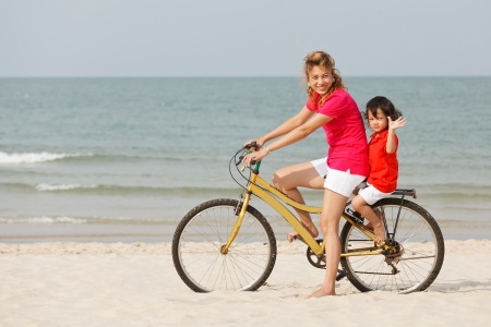 Asian mother and son riding bicycle on tropical beach photo