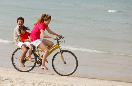 Asian mother and sons riding bicycle on tropical beach photo