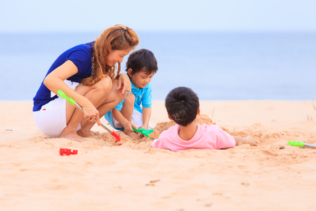 Asian mother and sons playing on sand beach photo