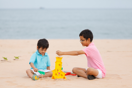 Two young brothers  playing on sand beach photo