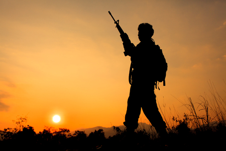 soldier silhouette: Silhouette shot of soldier holding gun