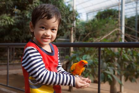Muchacho asiático poco de juego con el pájaro en el zoológico