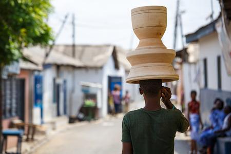 Escena Genaral de la mujer africana con las cosas en la cabeza y el teléfono móvil en la mano