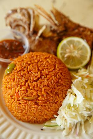 Eines der beliebtesten Essen in Ghana, Jollof Reis, dienen mit Fisch Standard-Bild - 27624597
