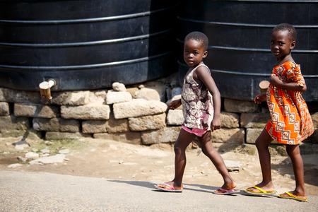 Two african girls walking beside big water tank Editorial