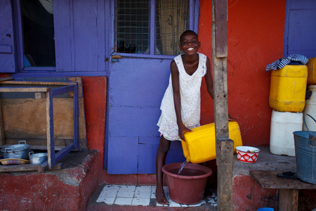 poor african: African girl pouring water to use in family
