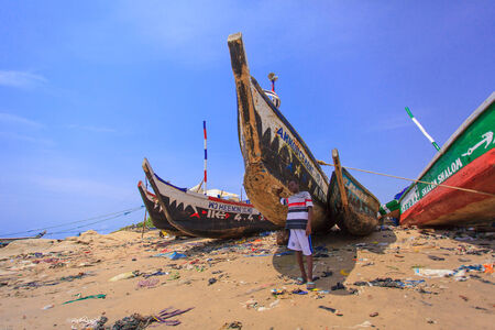Boy and raditional Ghanaian style wood boat on beach