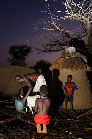 Ghanaian kids help father to bath for goat in evening
