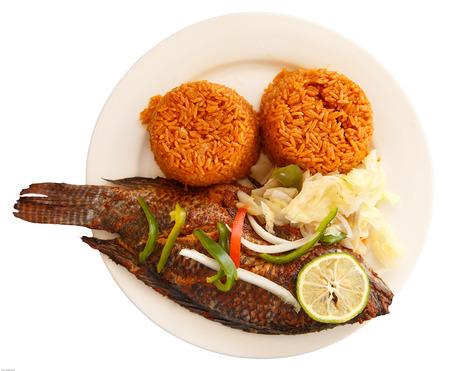 Einer der beliebtesten Speisen in Ghana, Jollof Reis, dienen mit Fisch Standard-Bild - 30231259