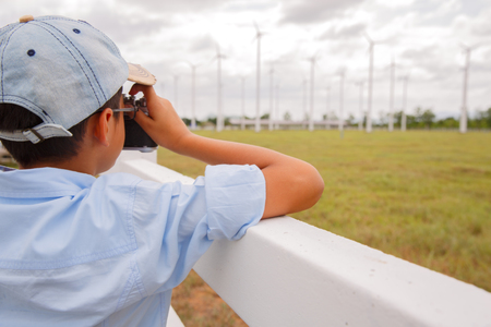 Young boy taking photo of wind turbine in field photo