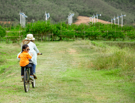 Woman and boy riding bicycle in farm with wind turbines in background photo