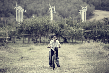 Boy training to ride bicycle in vintage style photo