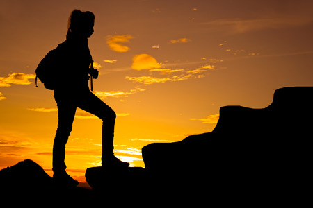 willing: Woman walking on top of mountain at twilight with backpack Stock Photo