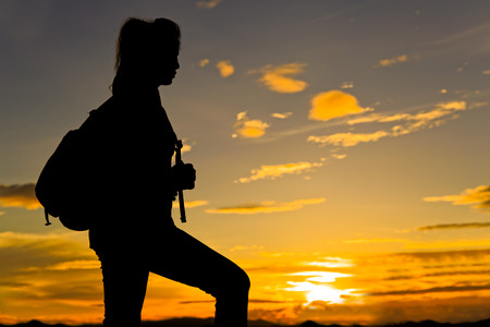 willing: Woman walking on top of mountain at twilight with sun ray under her feet Stock Photo