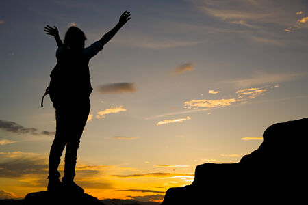 lonely person: Woman standing on top of mountain at sunset