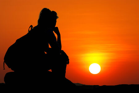 lonely person: Silhouette shot of woman sit on rock and look at sunset