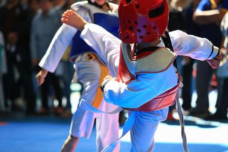 Kids fighting on stage during Taekwondo tournament Stock Photo