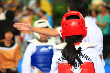 Referee gives signal to young Taekwondo athletes