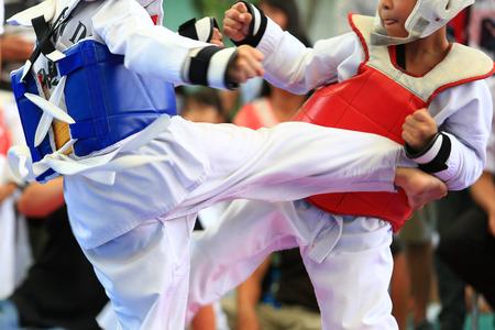 artes marciales: Los jóvenes atletas de Taekwondo están luchando durante concurso
