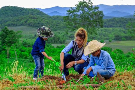Asian family planting tree in farm near mountain Stock Photo